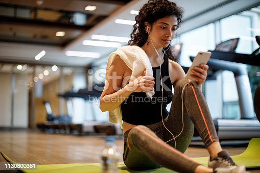 Young woman listening to music over cell phone at the gym