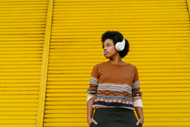 Young woman listening to music A young black woman is listening to music with a bluetooth wireless headphones connected to her portable music player in front of a yellow wall. wireless headphones stock pictures, royalty-free photos & images