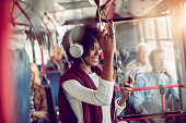 Close up of a young woman listening to music while riding in a bus