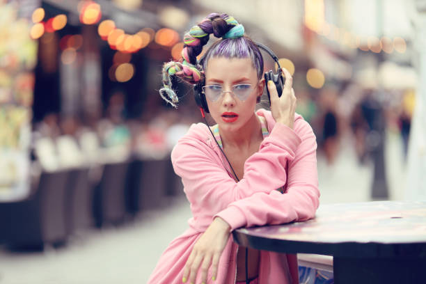 Young woman listening to music via headphones on the street - Hipster Girl with a nonconformist fashion look stock photo