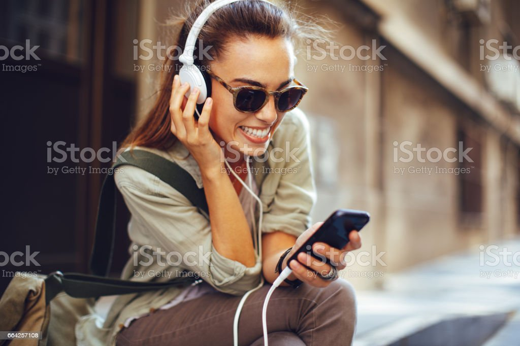 Young woman listening to music via headphones on the street stock photo