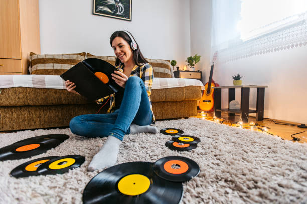Young woman listening to old records in lockdown stock photo