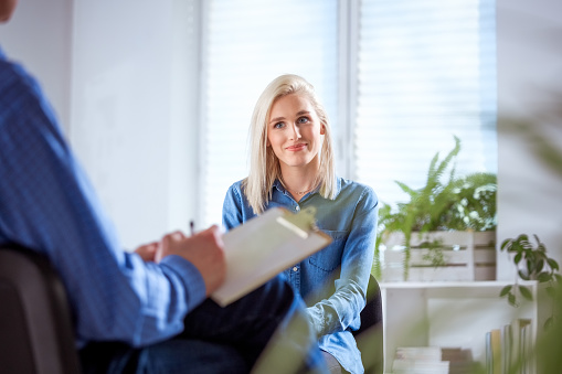 Young Woman Listening To Social Worker In Meeting Stock Photo - Download Image Now