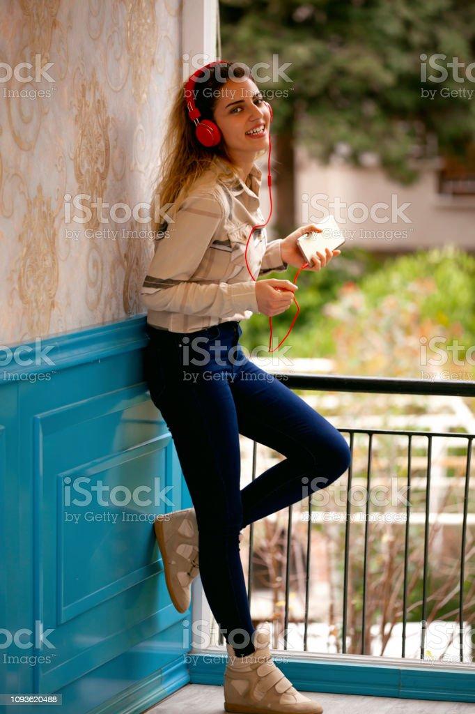 Genç kadın retro tarzı kafede onun telefondan müzik dinlerken. stok fotoğrafı