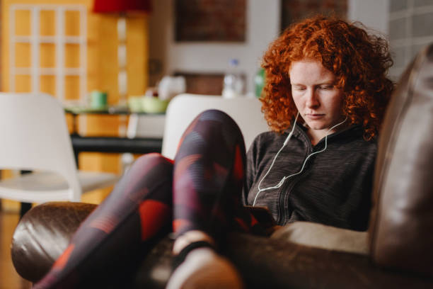 Young woman listening to the podcast at home stock photo