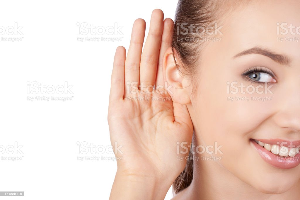 Young woman listening with a hand to her ear royalty-free stock photo