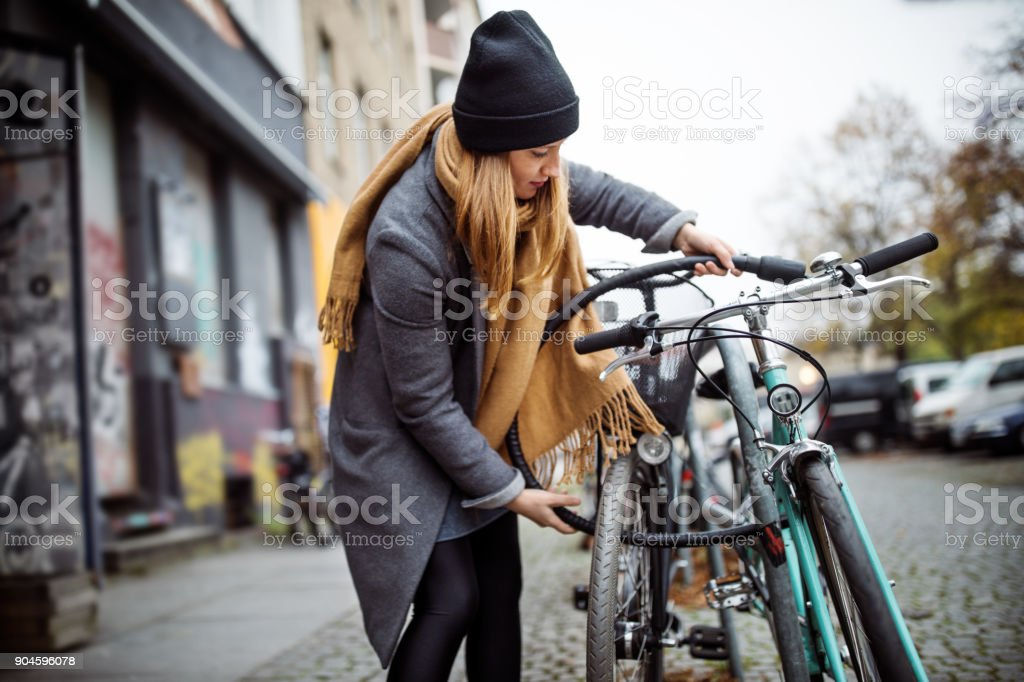 Young woman locking bicycle in city during winter royalty-free stock photo
