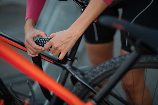 Young woman locking her mountain bike with a numeric lock