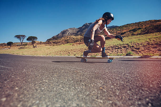 Young woman longboarding on a road stock photo