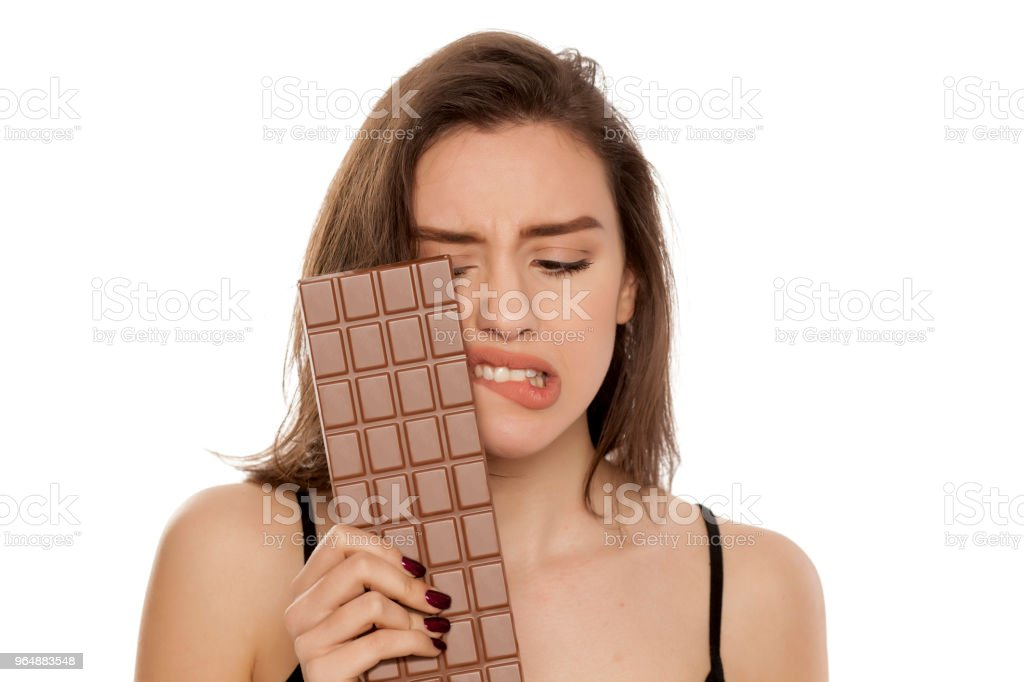 young woman longs looking at chocolate on white background royalty-free stock photo