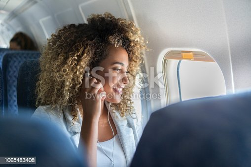 A young woman with curly hair sits in a window seat on a plane. She has her earbuds in as she looks out of the window and smiles.