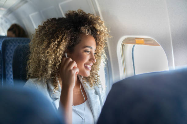 A young woman look out a plane window smiles A young woman with curly hair sits in a window seat on a plane. She has her earbuds in as she looks out of the window and smiles. passenger stock pictures, royalty-free photos & images