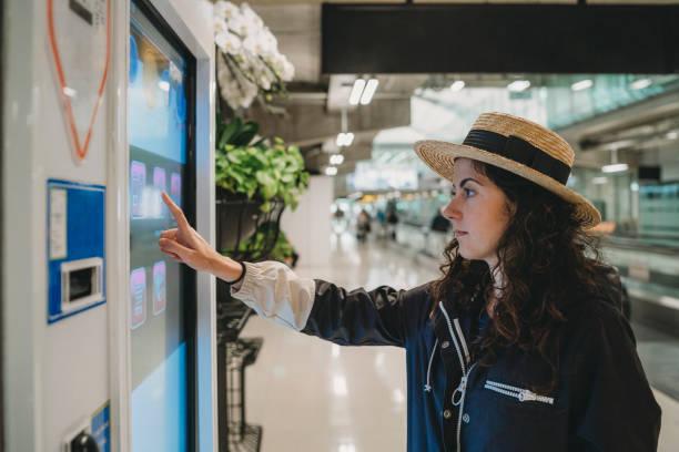jeune femme regardant un écran d'information à l'aéroport - écran tactile photos et images de collection