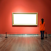 Young asian woman looking at white frames in an art gallery.