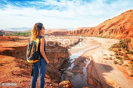 istock Young woman looking at beautiful landscape. Nature of Morocco view from above. Traveler girl stands on a rock looks up at the valley of Ounilla 872394530