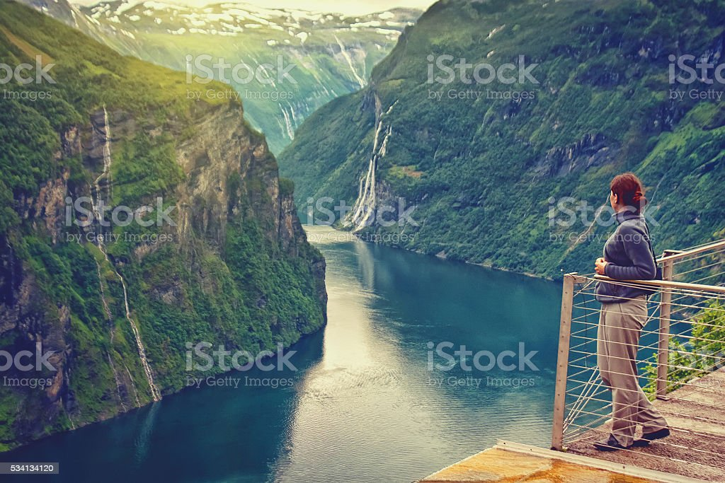 young woman looking at beautiful mountain landscape of Norway stock photo