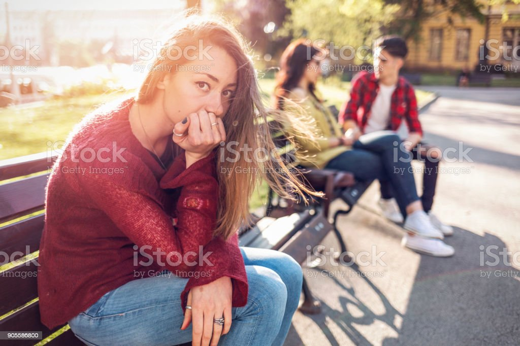 Young woman looking at camera and sitting alone on the park bench. stock photo