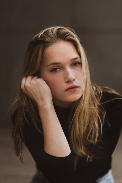 Young woman looking at camera with pensive expression stock photo