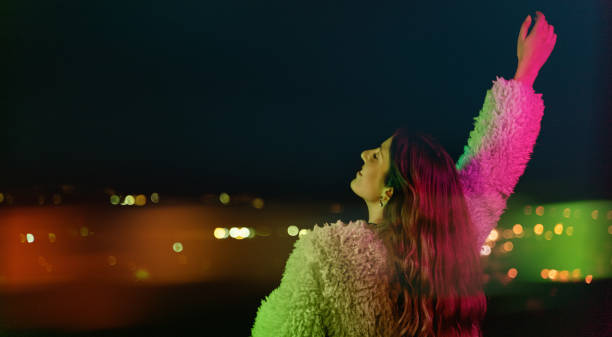 Young woman looking at city lights under colorful light stock photo