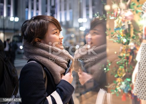 Young woman looking at clothes in store window