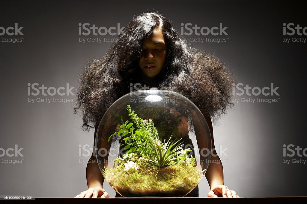 Young woman looking at fishbowl 免版稅 stock photo