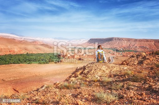 istock Young woman looking at fortified city. Glaoui Kasbah of Telouet kasbah or ksar in Morocco view from above. Traveler girl sits on a rock looks up at the valley of Ounilla 872393896