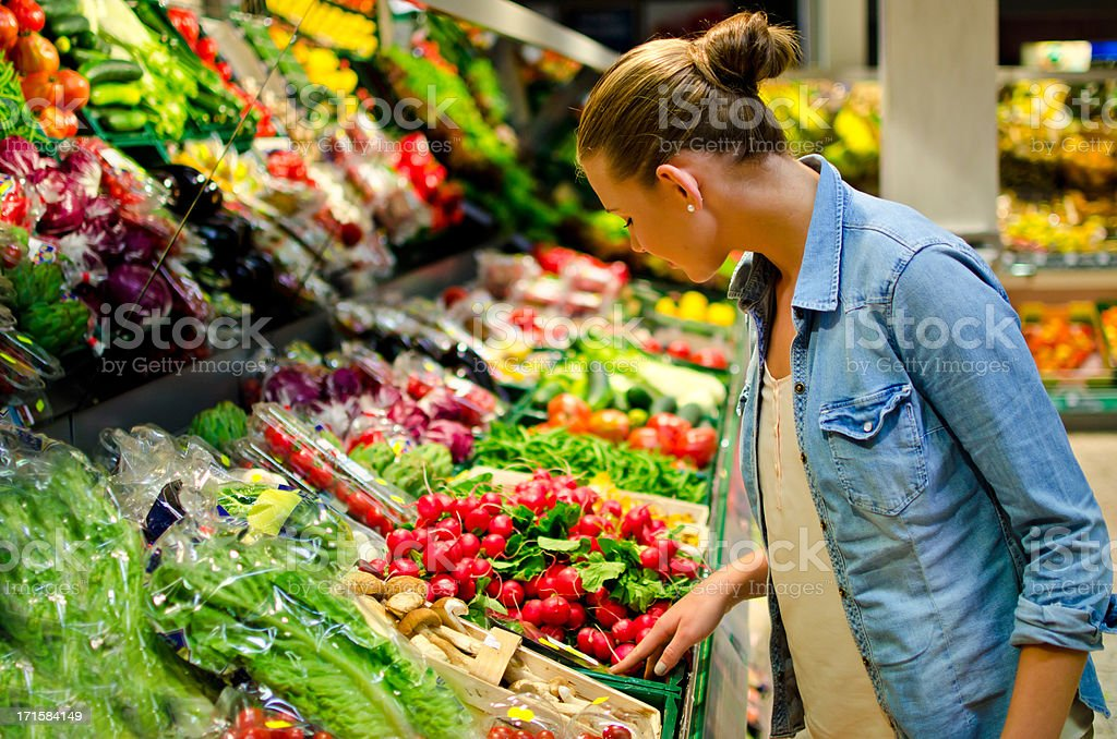 A young woman looking at fresh vegetables in the supermarket stock photo