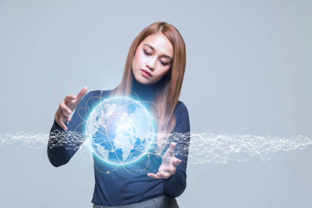 young woman looking at futuristic graphical user interface of the earth - pics for cool girl stock pictures, royalty-free photos & images