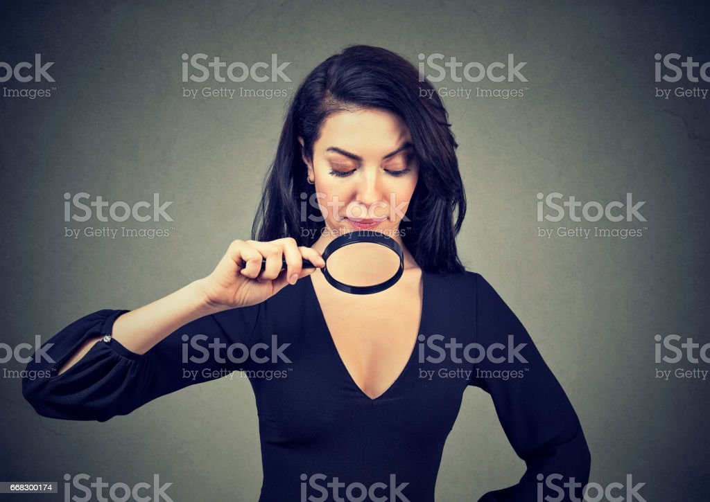 Young woman looking at her breasts through magnifying glass stock photo
