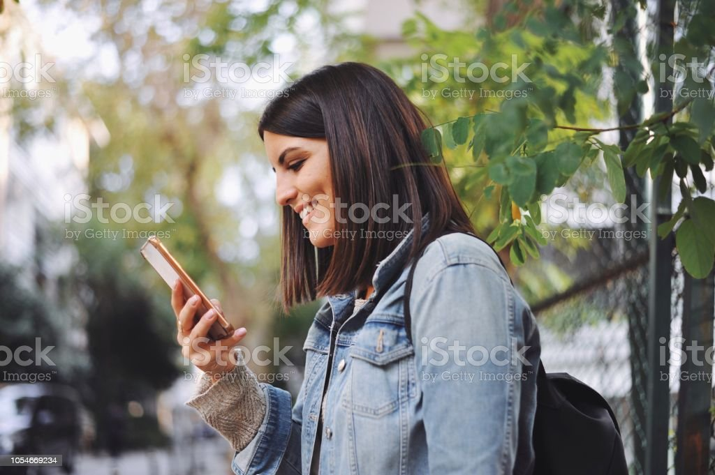 Young woman looking at her smart phone stock photo
