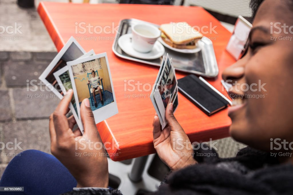 Young woman looking at instant camera photo frames stock photo