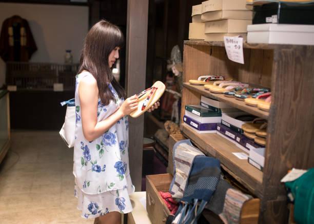 junge frau betrachten japanischen zori-sandale im ladengeschäft - damenschuhe k stock-fotos und bilder