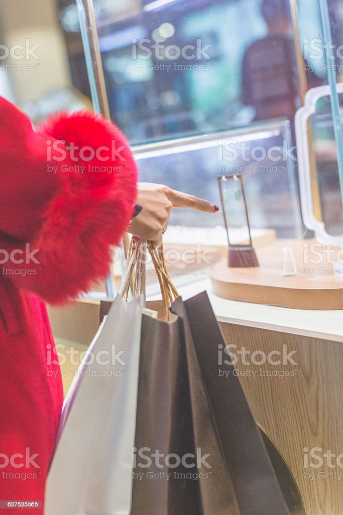 young woman looking at jewelry through shop window stock photo