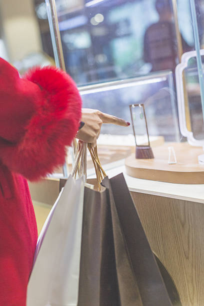 young woman looking at jewelry through shop window - diamanten kaufen stock-fotos und bilder