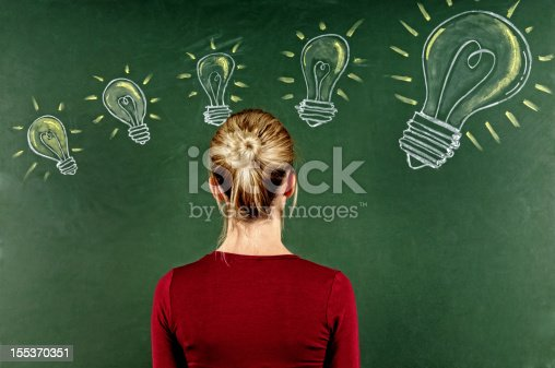 istock Young Woman Looking at Light Bulbs Sketched on Blackboard 155370351