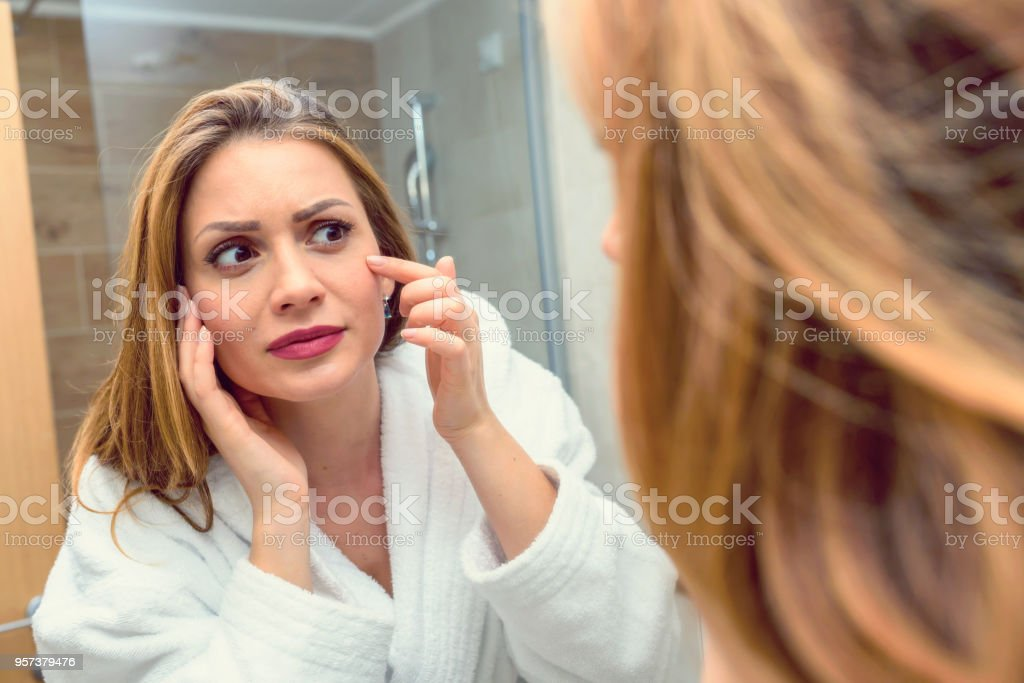 Young  Woman Looking At Mirror In Bathroom Worried About Acne and Aging stock photo