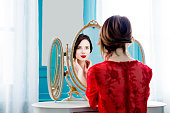 portrait of beautiful young woman looking at herself in the wonderful mirror and sitting next to it
