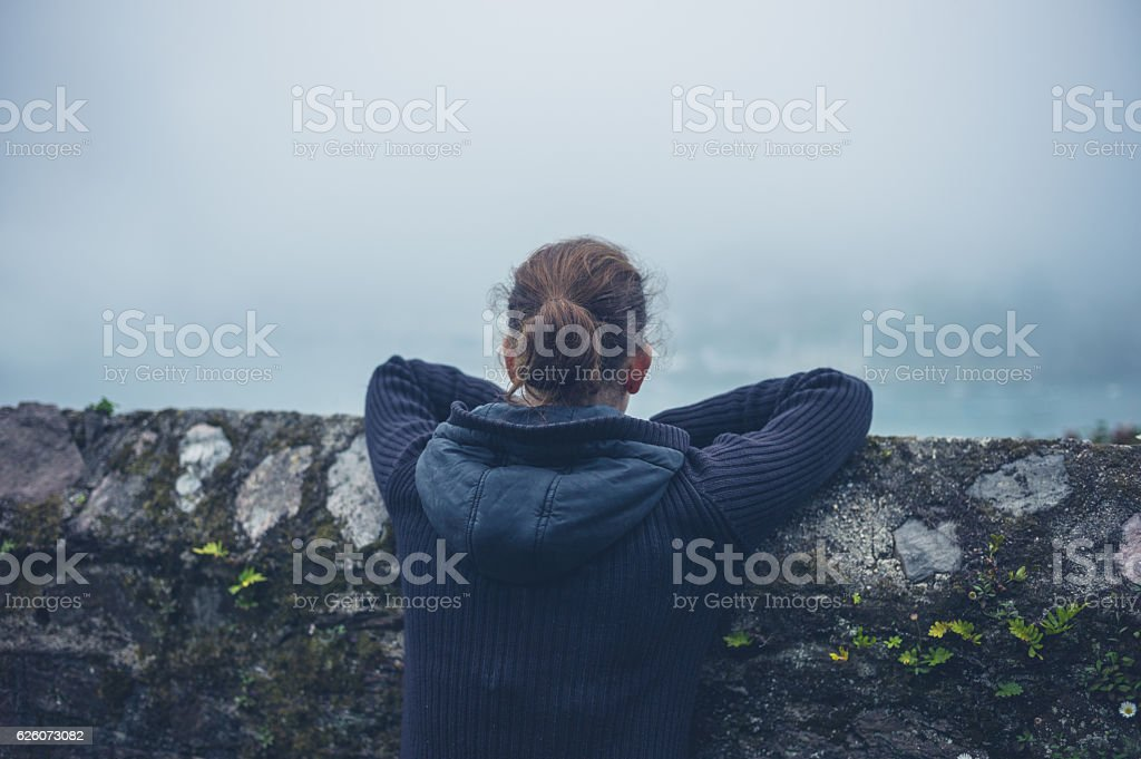 Young woman looking at mist stock photo
