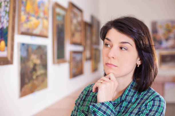Young woman looking at painting. Young woman looking at painting in art gallery. critic stock pictures, royalty-free photos & images