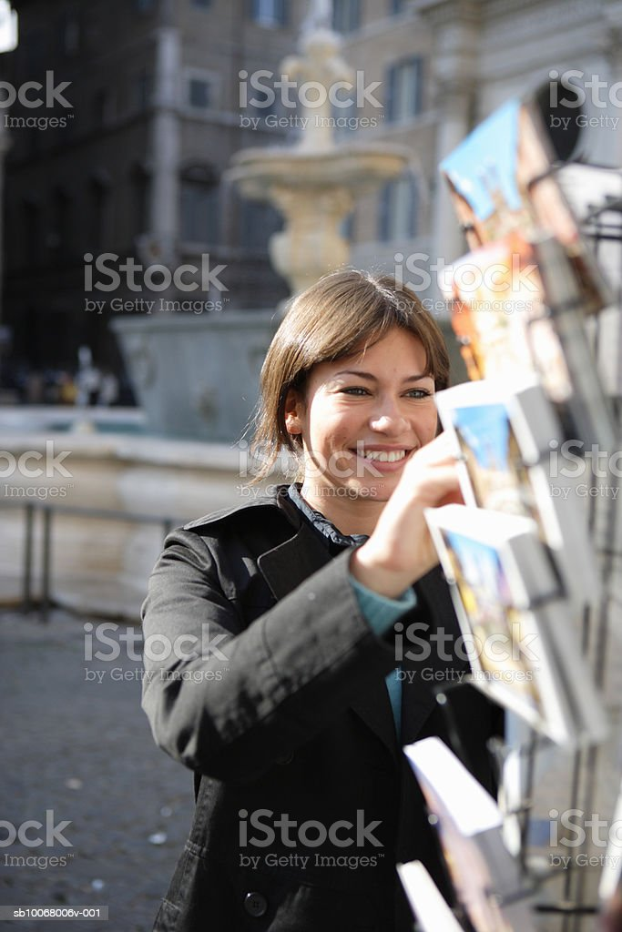 Young woman looking at postcards royalty free stockfoto