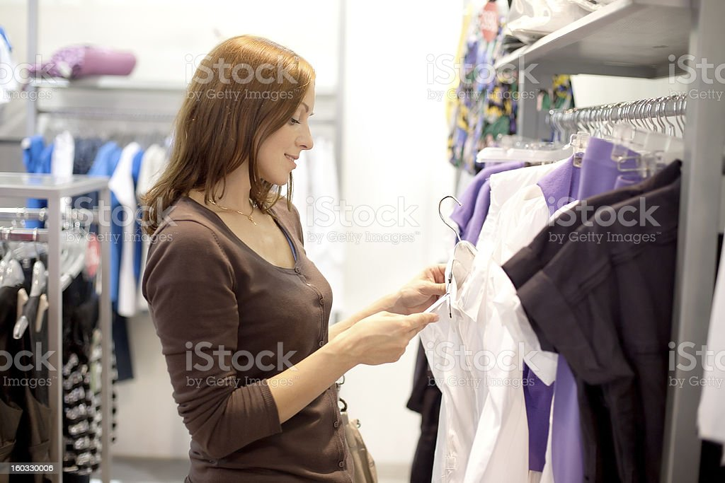 Young woman looking at price tags as she shops for clothing royalty-free stock photo