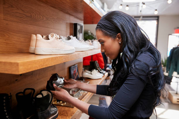 Young woman looking at shoes on display in a shop, close up stock photo