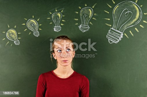istock Young Woman Looking at Sketched Light Bulbs 186834766