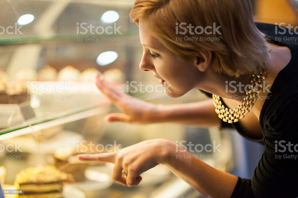 Young woman looking at sweets stock photo
