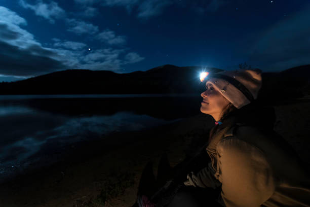 Young Woman Looking at the Clear Sky at Night in Camping. stock photo