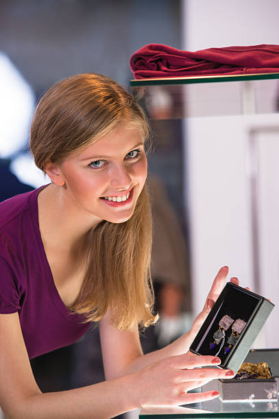 Young woman looking at the shop showcase and taking earrings stock photo