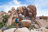 Young woman looking at the Skull Rock in Joshua Tree National Park, California, USA. Adventure and travel concept.