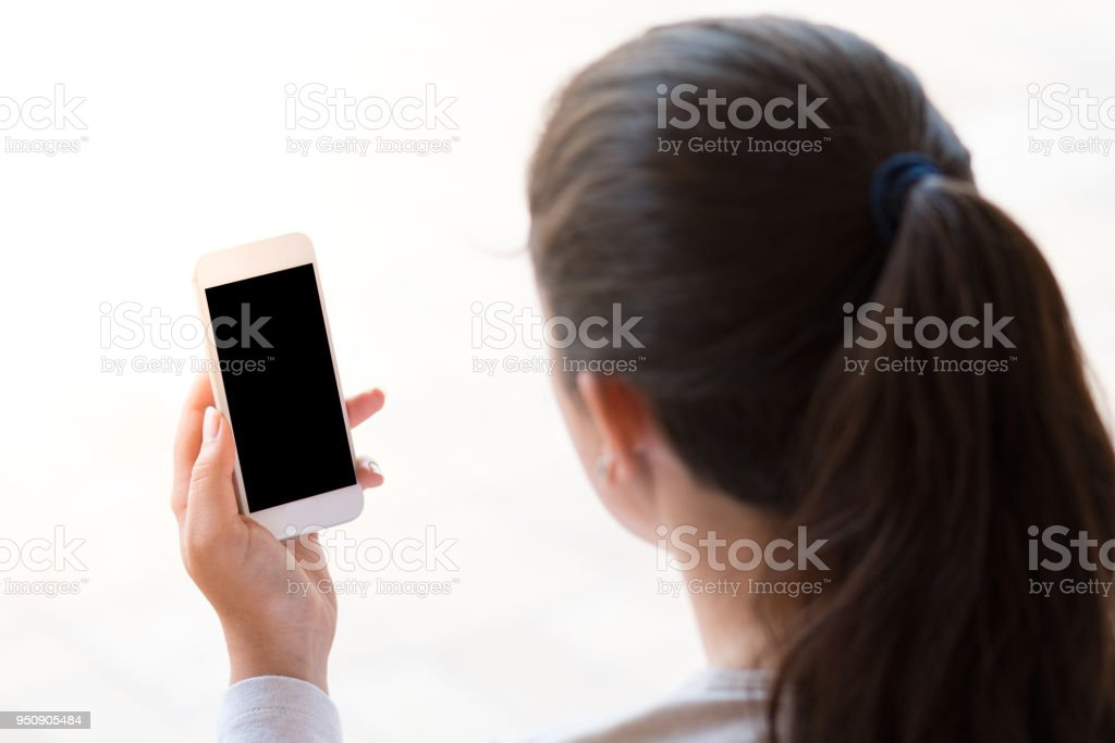 young woman looking at the smartphone, isolated on white background stock photo
