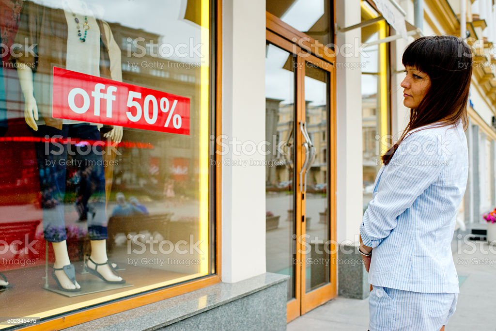 Young Woman looking at window display stock photo