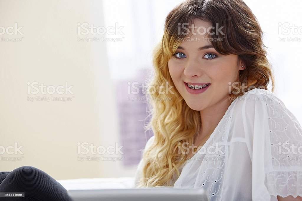 Young woman looking at you smiling with a tablet royalty-free stock photo